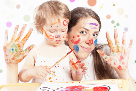 Mom and baby draws with colored inks paint. Games with child affect early development. Important to spend enough time with your kids.