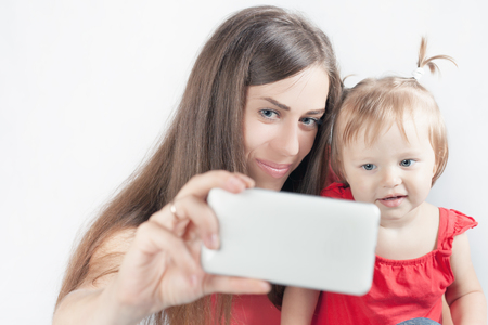 mothercare: Image of funny baby and mother make selfie photo on mobile phone. Newborn looking at the camera surprised! Mothercare is most important in baby life