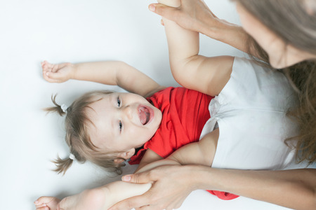 Funny Baby Girl Doing Exercise And Yoga With Her Happy Mother On A White Bed