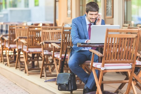 hapy: Successful man talking by mobile phone outdoor at French cafe, Paris. Using laptop. Concept of success deal. Online banking. Business partner