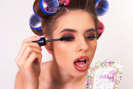 Young girl doing makeup and hairstyle using curlers and brush eyelashes. Eyelash overhead extension. Looking at mirror. Retro, pin up. White background