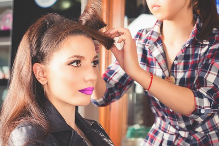 hair saloon: Beautiful young woman at beauty salon. Fashion hairstyle. Make up. Hair saloon. Hairdresser using hair spray