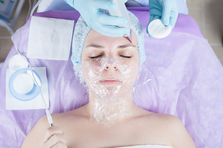 Woman in spa salon receive skin treatment. Creating occlusion for better atomization of the upper layer of the skin. Loosening of the skin. Face wrapping