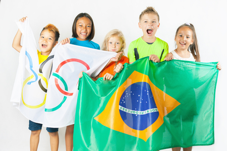 olympic symbol: RIO DE JANEIRO, BRAZIL - JULY 17, 2016: Children holding a flag of five rings symbol of Olympic Games and Brazil flag. Rio de Janeiro 2016 Brazil. Happy fans watching tv. Volunteer. Editorial