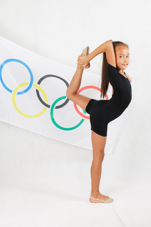 RIO DE JANEIRO, BRAZIL - JULY 17, 2016: Girl holding a flag of five rings symbol of the Olympic Games. Rio de Janeiro 2016 Brazil. Child doing artistic gymnastics element. Compete in individual events