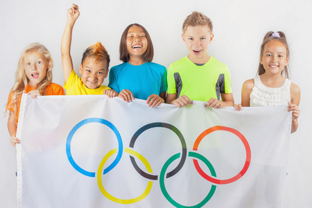 olympic ring: Group of children holding a flag of five rings symbol of the Olympic Games. Rio de Janeiro 2016 Brazil. Happy fans of kids watching tv. Volunteer Editorial