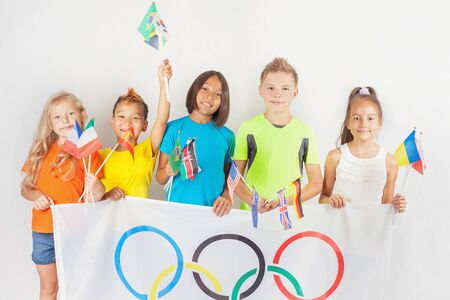 olympic symbol: RIO DE JANEIRO, BRAZIL - JULY 17, 2016: Group of children holding a flag of five rings symbol of Olympic Games and international flags. Rio de Janeiro 2016 Brazil. Happy fans watching tv. Volunteer.