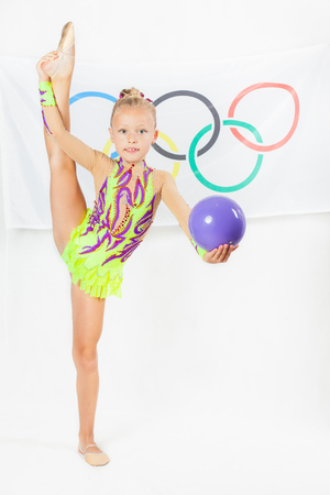 olympic symbol: RIO DE JANEIRO, BRAZIL - JULY 17, 2016: Child doing split - artistic gymnastics element with ball. Flag of five rings symbol of the Olympic Games at the background. Rio de Janeiro 2016 Brazil. Compete in individual events