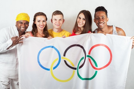 RIO DE JANEIRO, BRAZIL - JULY 19, 2016: Group of multiracial happy people holding flag of five rings symbol of Olympic Games. Rio de Janeiro 2016 Brazil. Happy fans watching tv. Volunteer Multi-ethnic