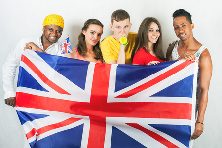 Group of multiracial people holding a England flag. Study English, students. School. Speak english. International games at Rio de Janeiro, Brazil. Happy fans. Multi-etnic person. Fan zone