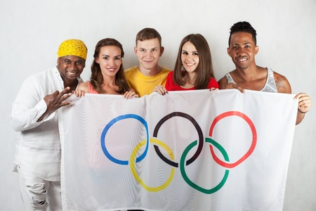 olympic symbol: RIO DE JANEIRO, BRAZIL - JULY 19, 2016: Group of multiracial happy people holding flag of five rings symbol of Olympic Games. Rio de Janeiro 2016 Brazil. Happy fans watching tv. Volunteer Multi-ethnic
