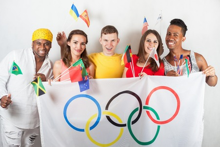 olympic symbol: RIO DE JANEIRO, BRAZIL - JULY 19, 2016: Group of multiracial happy people holding flag of five rings symbol of Olympic Games and international flags. Rio de Janeiro 2016 Brazil. Fans, Multi-ethnic Editorial