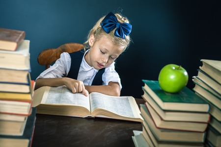 Smart school girl reading a book at library. Table with many books and one green apple. Child dressed in school uniform and glasses. Blackboard. Student. Concept of education. Scientist kid