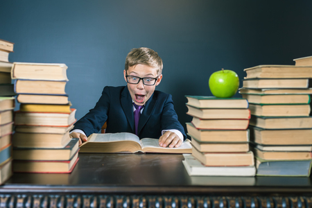 anecdote: Funny school boy reading a book at library. Joke! Table with many books and one green apple. Child dressed in school uniform and glasses. Blackboard. Student. Concept of education. Scientist kid