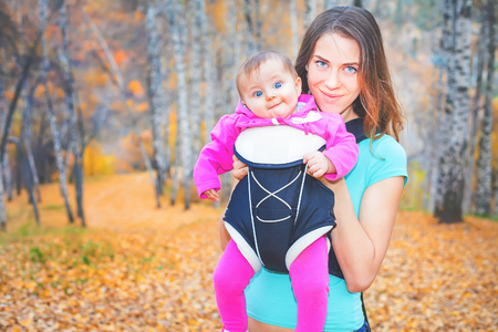 ergonomic: Happy mother carrying her child by ergonomic baby carrier. Adventure, hiking. They walk outdoor at national mountain park at autumn season