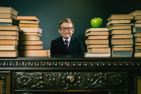 cunning: Cunning school boy sitting at the table with many books and one green apple. Smiling child dressed in school uniform and glasses. Blackboard. Student. Concept of education. Looking at camera Stock Photo