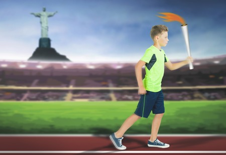 bearer: Young athlete boy with sport torch bearer running by track at Stadium inside at Rio de Janeiro, Brazil. Corcovado Mountain with Jesus statue at background.