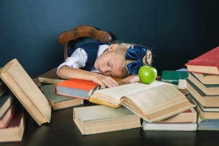 school exam: School girl sleeping at the table with many books and one green apple. Many homeworks or exam - is stress for little kids. Motivate your child to study a boring subject. Student. Pupil studying