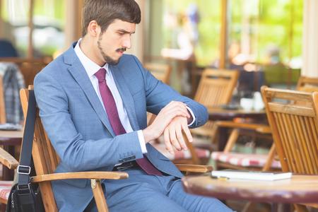 puntualidad: Hombre hermoso que mira el reloj de tiempo. Y espera sentado en el café de la acera al aire libre. Ejecutivo de negocios vestidos con trajes de moda. Hombre con estilo. Puntualidad Foto de archivo