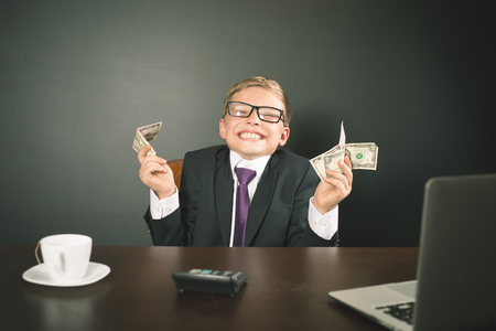 earned: Boy has earned a lot of money. Banker holds in hand American dollars. Cunning business boy. Successful school boy. Happy. Success concept. Business suit. Stock exchange. Lucky man