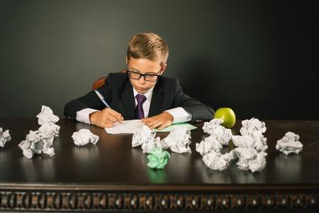 essay: Inspired school boy writing essay or exam. Bloger has a good idea and writing it.