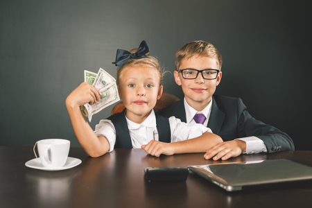 american banker: Boy and girl has earned a lot of money. Banker holds in hand American dollars. Smart business boy. Successful school children. Happy. Success concept. Business suit. Stock exchange. Lucky girl Stock Photo