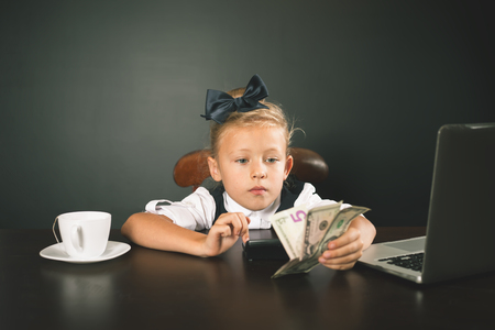 american banker: Girl has earned a lot of money. Banker holds in hand American dollars. Smart business female. Successful school girl. Happy. Success concept. Business suit. Stock exchange. Lucky girl