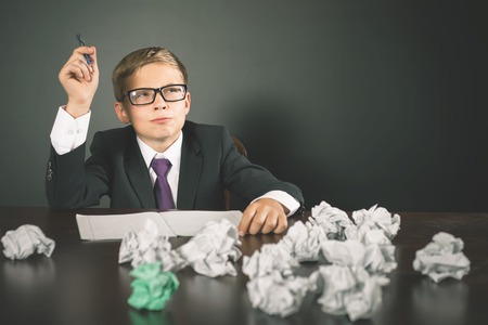 essay: Inspired school boy has a great idea! Writing essay or exam. Young business person has a good idea and writing it. Conceptual image, copy space Stock Photo