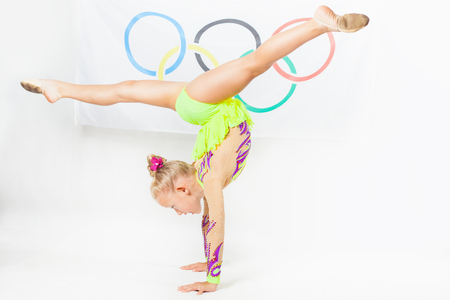 olympic symbol: RIO DE JANEIRO, BRAZIL - JULY 17, 2016: Child doing split - artistic gymnastics element. Flag of five rings symbol of the Olympic Games at the background. Rio de Janeiro 2016 Brazil. Compete in individual events Editorial