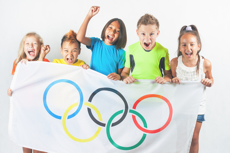 olympic ring: RIO DE JANEIRO, BRAZIL - JULY 17, 2016: Group of children holding a flag of five rings symbol of Olympic Games. Rio de Janeiro 2016 Brazil. Olympic games closing ceremony Editorial