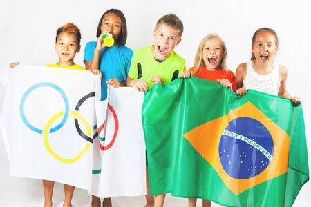 olympic ring: RIO DE JANEIRO, BRAZIL - JULY 17, 2016: Children holding a flag of five rings symbol of Olympic Games and Brazil flag. Rio de Janeiro 2016 Brazil. Volunteer. Olympic games closing ceremony Editorial