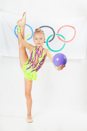 olympic symbol: RIO DE JANEIRO, BRAZIL - JULY 17, 2016: Child doing split - artistic gymnastics element with ball. Flag of five rings symbol of the Olympic Games at the background. Rio de Janeiro 2016 Brazil. Illustrative editorial Editorial