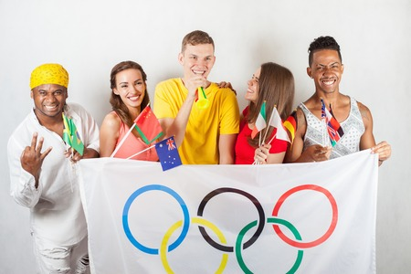 olympic symbol: RIO DE JANEIRO, BRAZIL - JULY 19, 2016: Group of multiracial happy people holding flag of five rings symbol of Olympic Games. Rio de Janeiro 2016 Brazil. Olympic games closing ceremony