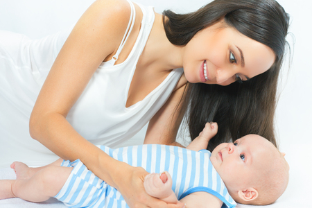 mothercare: Happy mother holding a baby boy at white background. Newborn looking at mom. Mothercare is most important in baby life