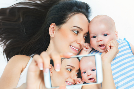 Funny baby and mother make selfie on mobile phone and lying near her mother on a white bed. Newborn looking at the camera and smiling. Mothercare is most important in baby life Stock Photo