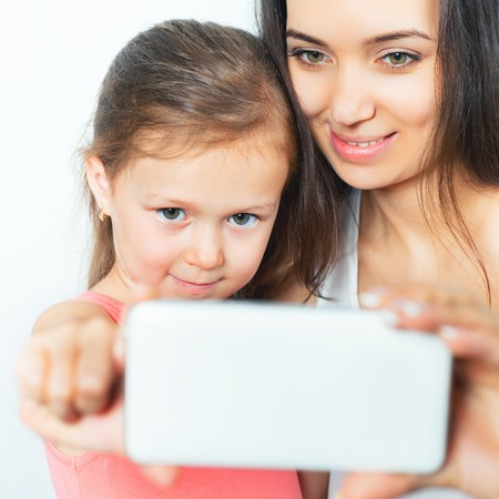 mothercare: Cute child and mother make selfie on mobile phone. Daughter and mum looking at the camera and smiling. Mothercare is most important in childs life Stock Photo
