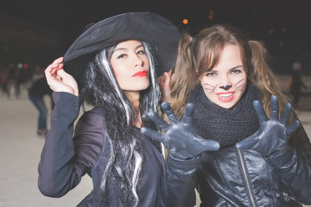 roleplaying: Halloween party! Young women like witch and cat role. Cat and witch carnival mask. Role-playing games. Fashion girls