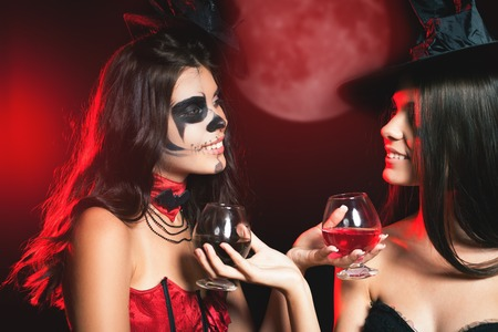 roleplaying: Halloween party 2016! Fashion women like witch holding cocktail of blood. Makeup. Halloween costumes. Role. Witch carnival costume. Role-playing games. Sexy babes. Night with big full moon