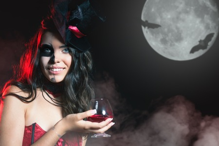 roleplaying: Halloween party 2016! Beautiful woman like witch holding cocktail of blood. Halloween costumes. Role. Witch carnival costume. Role-playing games. Sexy girls. Night with big full moon Stock Photo
