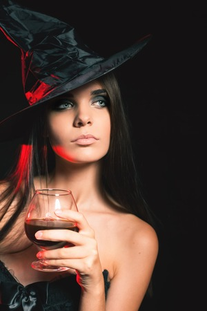 Halloween party 2016! Beautiful woman like witch holding cocktail of blood. Halloween costumes. Role. Witch carnival costume. Role-playing games. Sexy girls. Night club