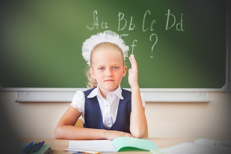 english girl: Girl sitting at the desk at school. Background blackboard, where she wrote the english alphabet. Schoolgirl raised her hand up. On the table lay a notebook, pen, pencil.