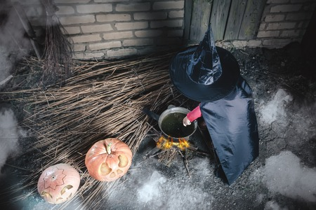 flying witch: Little baby witch making a magic potion at Halloween night. Caution! Somewhere near here flying witch mother! Horror. Pumpkins with broom. Halloween costumes for child. Witch. Stock Photo