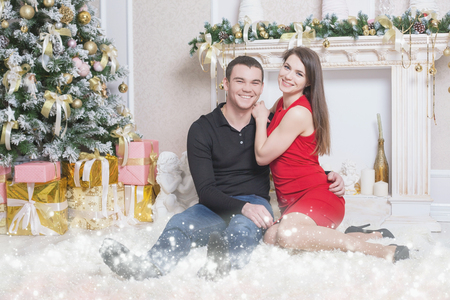 cristmas: Happy couple dating and celebrating Cristmas. New Year 2017. Champagne. They sitting at living room near fireplace and Christmas tree with magical light, stars dust.