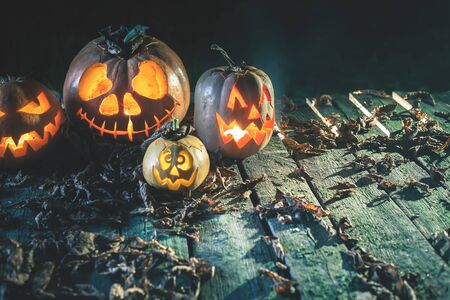 Halloween pumpkins at wood background. Carved scary faces of pumpkin. Night horror. October holiday. Pumpkin family. Copy space at background