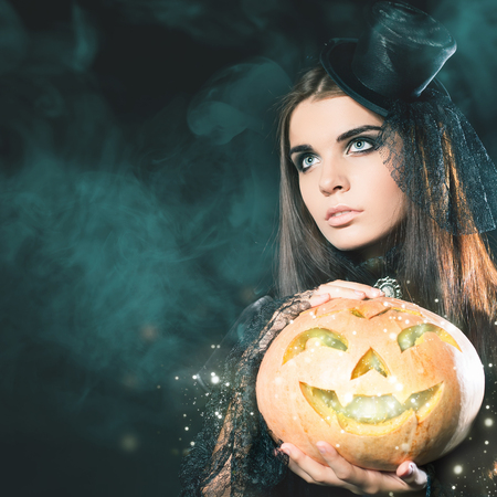 Entrance is limited to nightclub, dress code. Fashion young woman with pumpkin going to Halloween party 2016! Beautiful woman like witch. Moon, scary cemetery. Hallowen costumes, pumpcin Stock Photo