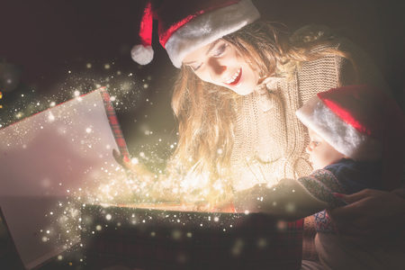 magic box: Mother opens the magic box with a gift for child. At Christmas night! Shining light. The kid looking at the box with interest. Mom and baby in Santa hats Stock Photo