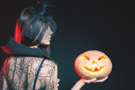 hallowen: Entrance is limited to nightclub, dress code. Fashion young woman with pumpkin going to Halloween party 2016! Beautiful woman like witch. Moon, scary cemetery. Hallowen costumes, pumpcin Stock Photo