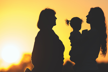mothercare: Silhouette of happy family with mother, daughter and grandmother outdoor. Fall season. Healthy concept. Mothercare is most important in baby life. Silhouete adults