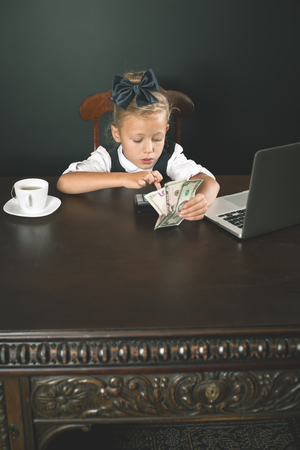 earned: Girl has earned a lot of money uses internet by laptop. Banker holds in hand American dollars. Smart business female Stock Photo