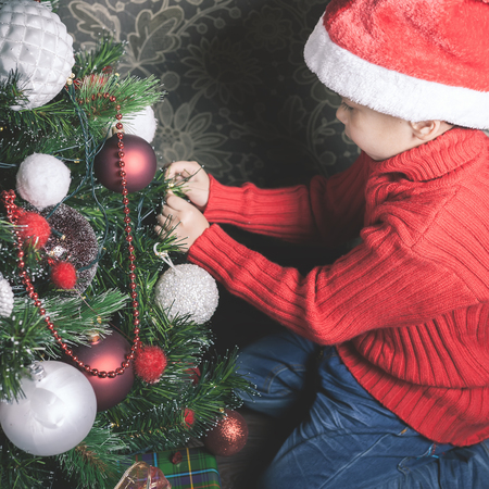 decorating christmas tree: Portrait of asian boy decorating Christmas tree, dressed Santa hat. Family decorating a Cristmas tree Stock Photo